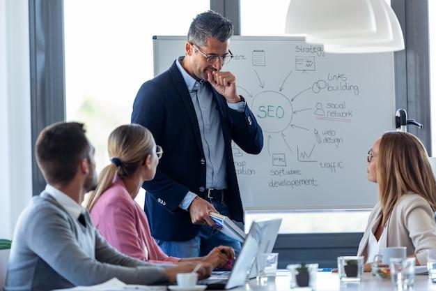 Ujęcie przystojnego biznesmena chrząkającego gardło, wyjaśniając projekt swoim kolegom na coworkingu.