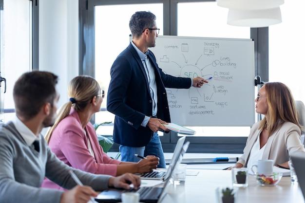 Ujęcie przystojnego biznesmena wskazującego na białą tablicę i wyjaśniającego projekt swoim kolegom na coworkingu.