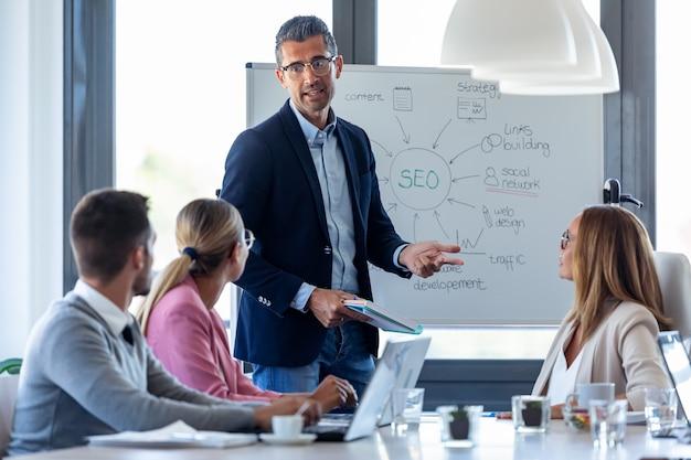 Ujęcie przystojny biznesmen wyjaśniający projekt swoim kolegom na coworking miejscu.