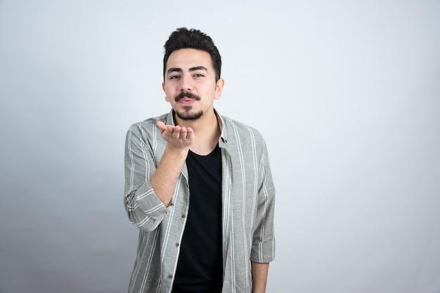 Ujęcie przystojny młody człowiek z brodą dmuchanie buziaka.
