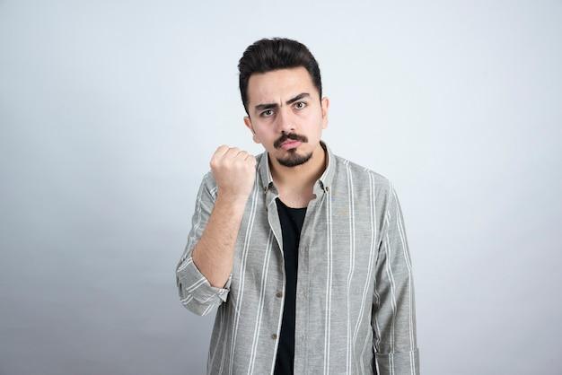 Ujęcie przystojny młody człowiek z brodą patrząc poważnie na białej ścianie.