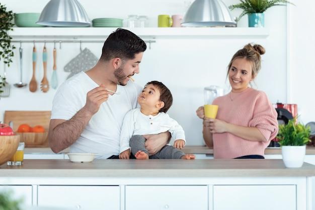 Ujęcie przystojny młody ojciec karmi syna, podczas gdy matka szuka ich w kuchni w domu.
