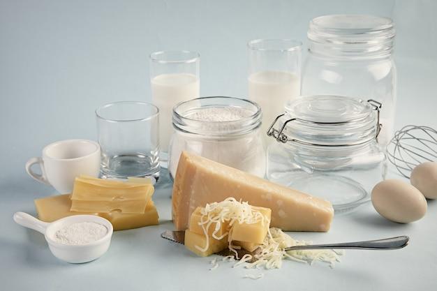 Ujęcie pysznego talerza serów z mlekiem i jajkami na białym tle na jasnoniebieskim tle