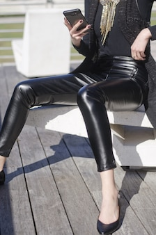 Ujęcie siedzącej kobiety trzymającej telefon w czarnych skórzanych spodniach i złotym naszyjniku