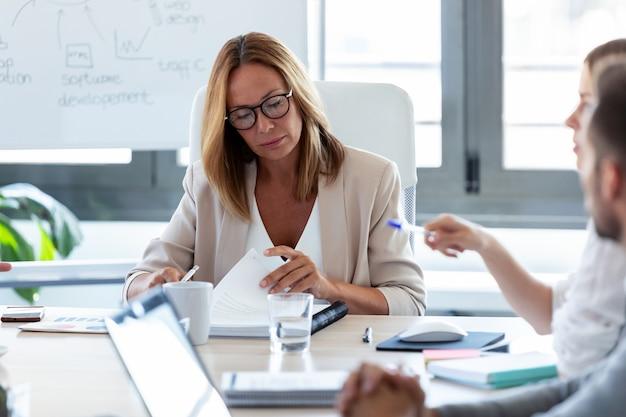 Ujęcie skoncentrowanej kobiety biznesu przeglądanie jej notatek na spotkanie w przestrzeni coworkingowej.
