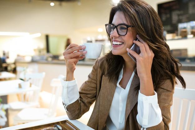 Ujęcie śmiechu młodej bizneswoman rozmawiającej z jej telefonem komórkowym w kawiarni.
