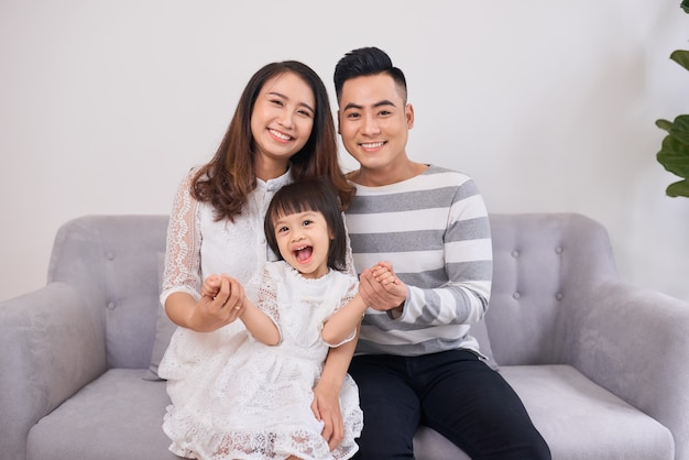 Ujęcie śmiejącej się małej dziewczynki siedzącej na kanapie z rodzicami rano.