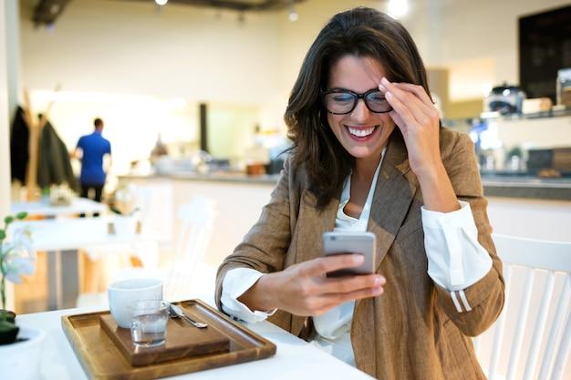 Ujęcie śmiejącej się młodej bizneswoman wysyłającej sms-y z jej telefonu komórkowego w kawiarni.