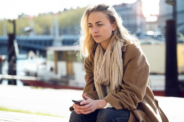 Ujęcie smutnej młodej kobiety myślącej o swoich problemach, siedząc nad rzeką w mieście.