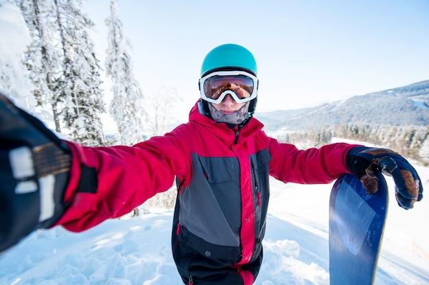 Ujęcie snowboardera mężczyzny przy selfie, w hełmie, masce narciarskiej i kolorowej zimowej odzieży snowboardowej