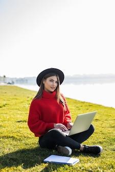 Ujęcie studenta korzystającego z laptopa na trawie na terenie kampusu