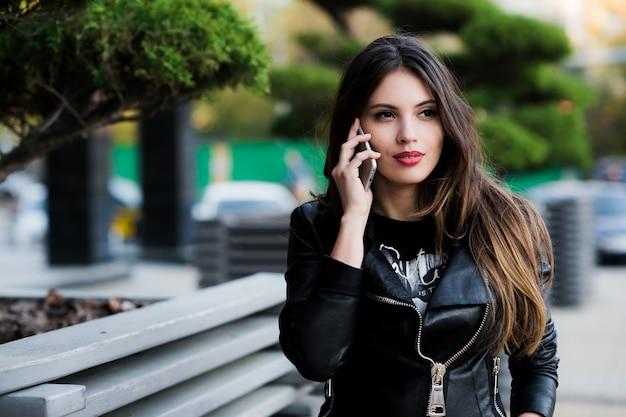 Ujęcie studenta rozmawiającego przez telefon na zewnątrz