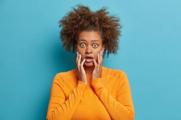 Ujęcie studyjne przerażonej, kręconej nastolatki, która chwyta twarz z wytrzeszczonymi oczami, wpatruje się z niedowierzaniem