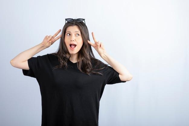 Ujęcie stylowej młodej kobiety pozowanie w okulary i pokazując znak v.
