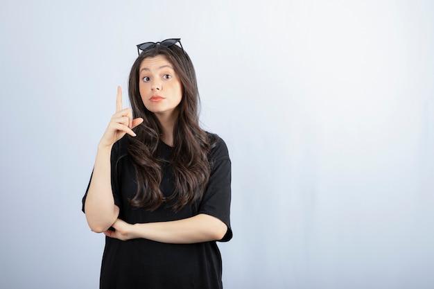 Ujęcie stylowej młodej kobiety stwarzających w okulary na białym tle. .