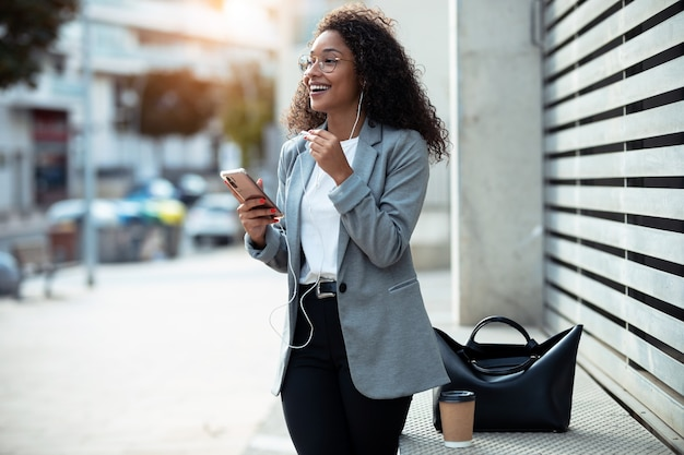 Ujęcie szczęśliwa młoda kobieta biznesu słuchania muzyki z jej inteligentnego telefonu, stojąc na ulicy.
