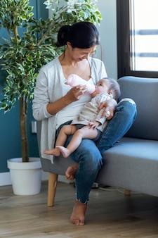 Ujęcie szczęśliwa młoda matka karmi swoją córeczkę butelką do karmienia, siedząc na kanapie w domu.