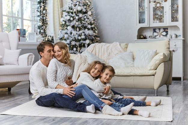 Ujęcie szczęśliwa młoda uśmiechnięta rodzina siedzi na podłodze z dwójką dzieci i cieszy się relaksem w domu.