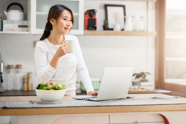 Ujęcie szczęśliwej azjatki, która robi sobie przerwę na kawę podczas korzystania z laptopa pracującego w domu w kuchni