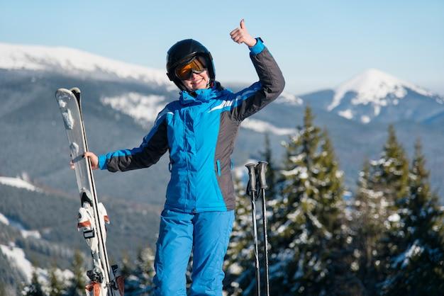 Ujęcie szczęśliwej kobiety, uśmiechając się, pokazując kciuki do góry pozowanie w górach, ciesząc się wakacjami w ośrodku narciarskim