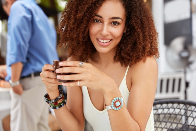 Ujęcie szczęśliwej kobiety z kręconymi włosami, pije aromatyczną kawę, siedzi przed wnętrzem kawiarni, będąc w dobrym nastroju. ładna kobieta z gorącym napojem.