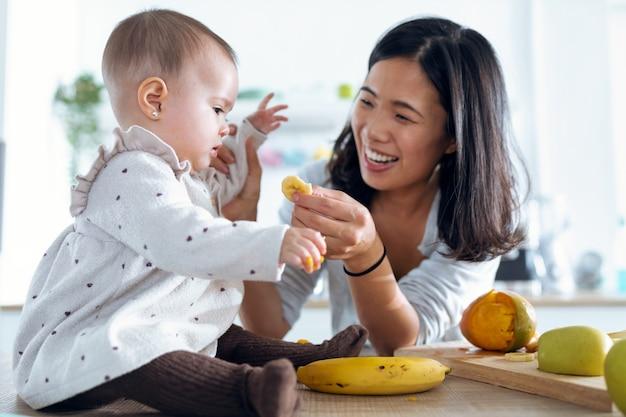 Ujęcie szczęśliwej młodej matki karmiącej jej śliczną córeczkę z bananem w kuchni w domu.