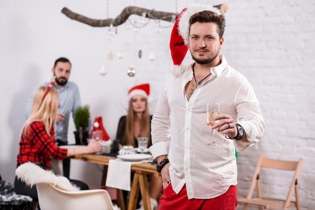 Ujęcie szczęśliwych przyjaciół cieszących się wakacjami skupia się na człowieku na pierwszym planie w czerwonym świątecznym kapeluszu