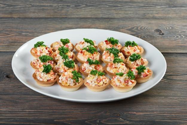 Ujęcie talerza z tartaletkami z sałatką ozdobioną zieleniną na drewnianym stole przystawka dla smakoszy luksusowe żywe menu restauracji zamów pyszne smaczne jedzenie.