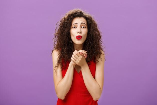 Ujęcie talii w górę kobiety patrzącej na wzruszającą scenę, która jest dotykana i zachwycona, trzymając razem dłonie na piersi składane usta, ciesząc się oglądaniem słodkiego szczeniaka pozującego zadowolony na fioletowym tle.