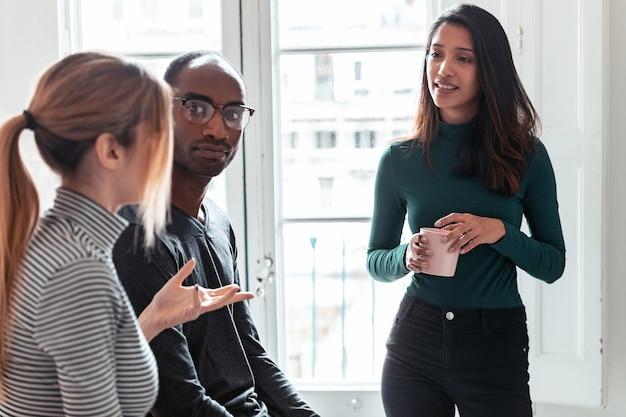 Ujęcie trzech młodych ludzi biznesu picia kawy podczas przerwy w biurze.
