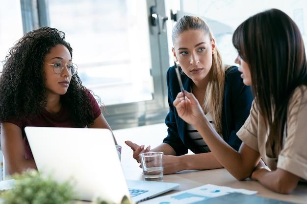 Ujęcie trzech nowoczesnych kobiet biznesu rozmawiających i przeglądających najnowsze prace wykonane na komputerze we wspólnej przestrzeni roboczej