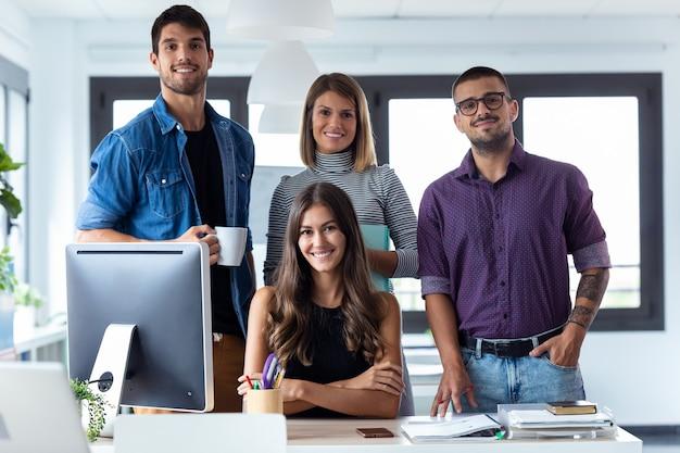 Ujęcie udanego zespołu biznesowego pozowanie zgrupowane wokół atrakcyjnej młodej kobiety patrząc w kamerę w przestrzeni coworkingowej.