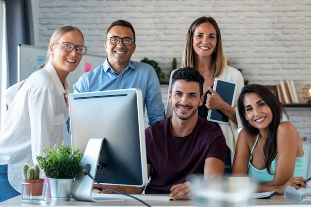 Ujęcie udanego zespołu biznesowego stojącego wokół komputera do prezentacji pracy, patrząc na kamerę w przestrzeni coworkingowej.