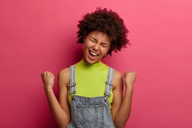 Ujęcie uradowanej kręconej kobiety czuje się jak zwycięzca, zaciska pięści z triumfem, nosi modne ubrania, wykrzykuje radośnie, przechyla głowę, pozuje na różowej ścianie, ma euforyczne uczucia