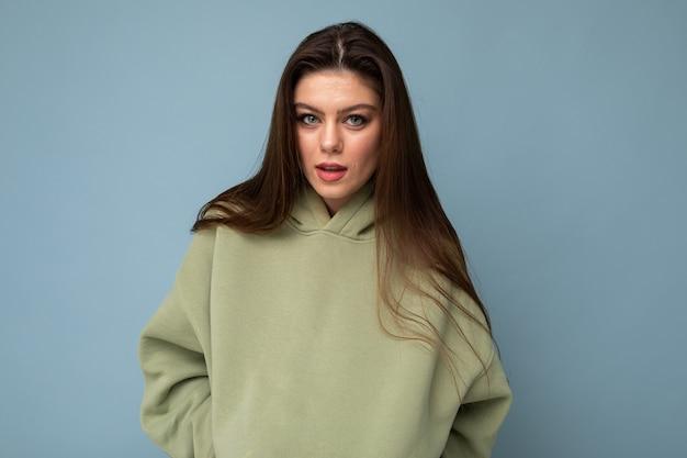 Ujęcie uroczej młodej bruneta fajnej kobiety w stylowej bluzie z kapturem khaki odizolowanej na niebiesko
