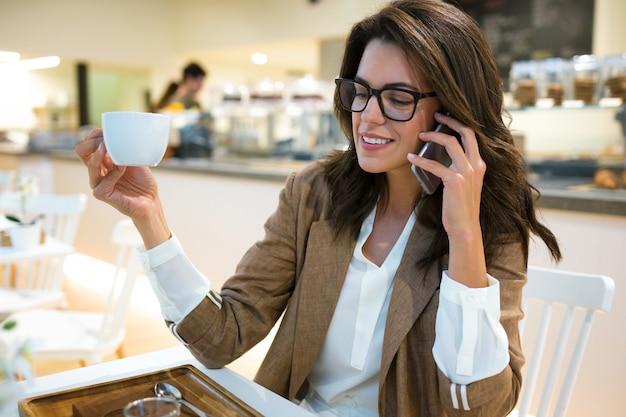 Ujęcie uśmiechnięta młoda bizneswoman rozmawia z jej telefonem komórkowym w kawiarni.