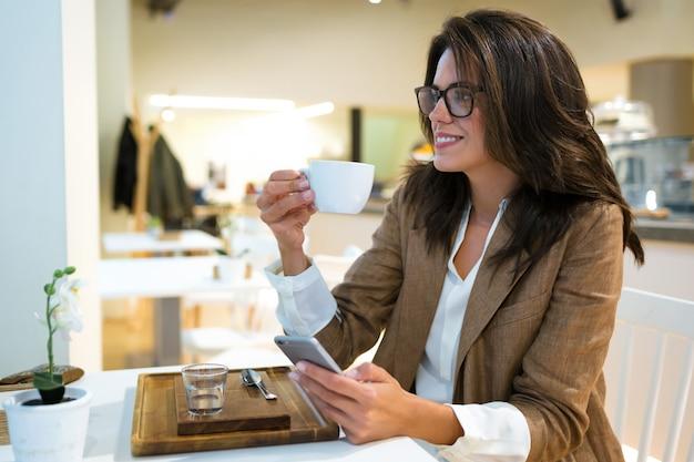 Ujęcie uśmiechnięta młoda bizneswoman wysyłająca sms-y z jej telefonu komórkowego w kawiarni.