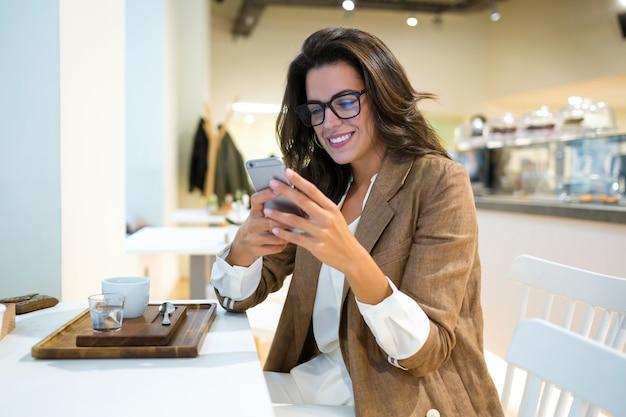 Ujęcie uśmiechnięta młoda bizneswoman z okularami wysyłająca sms-y z jej telefonu komórkowego w kawiarni.