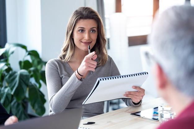 Ujęcie uśmiechnięta młoda kobieta biznesu słuchając swojego partnera, trzymając notatki na temat przestrzeni coworkingowej.