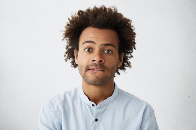 Ujęcie w głowę atrakcyjnego ucznia rasy mieszanej z zarostem i potarganymi włosami przygryzającymi dolną wargę