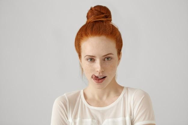 Ujęcie w głowę atrakcyjnej, kuszącej kobiety z rudymi włosami związanymi w supeł, oblizującą usta