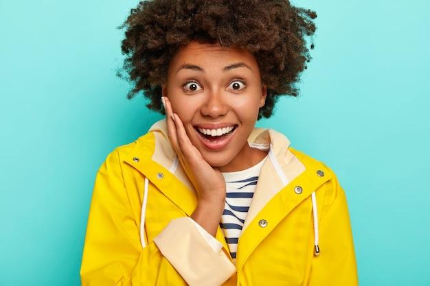 Ujęcie w głowę dobrze wyglądającej afroamerykanki dotyka policzków, wygląda radośnie, będąc w dobrym nastroju, ubrana w wodoodporny płaszcz przeciwdeszczowy, odizolowana na niebieskim tle