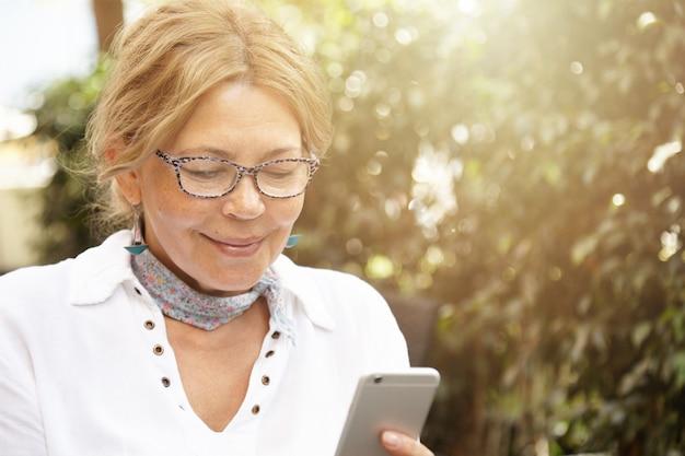 Ujęcie w głowę dobrze wyglądającej, nowoczesnej, dojrzałej blondynki w okularach, wysyłającej wiadomości do swojego wnuka za pośrednictwem sieci społecznościowych, używającej swojego zwykłego telefonu komórkowego, uśmiechającej się podczas czytania wiadomości lub oglądania zdjęcia