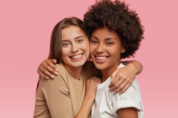 Ujęcie w głowę dobrze wyglądających kobiet z pozytywnymi minami, przytulających się do siebie