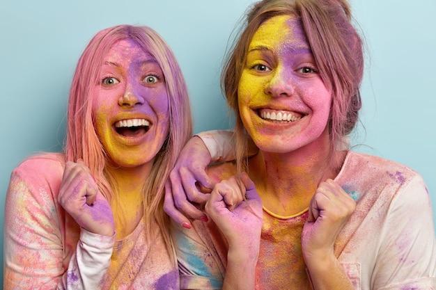 Ujęcie w głowę dwóch pozytywnie nastawionych, wesołych kobiet z zębami uśmiechem na twarzach, o zabrudzonej skórze, uniesionych dłoniach zaciśniętych w pięści