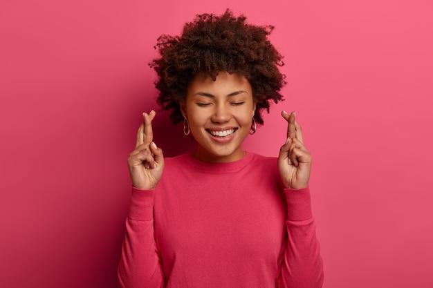 Ujęcie w głowę ładnie kręconej przesądnej kobiety krzyżuje palce, modli się o lepsze, uśmiecha się delikatnie, zamyka oczy, nosi różowy sweter, pozuje w domu na jasnej ścianie, przewiduje ważne rezultaty