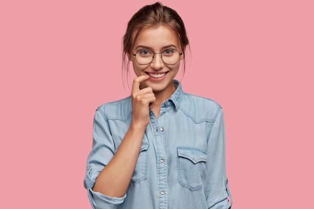 Ujęcie w głowę ładnie wyglądającej, sympatycznej kobiety trzymającej palec wskazujący przy ustach, uśmiechającej się pozytywnie