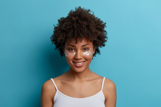 Ujęcie w głowę ładnie wyglądającej wesołej afroamerykanki nosi plastry nawilżające pod oczami, lubi zabiegi pielęgnacyjne, delikatnie się uśmiecha, pozuje