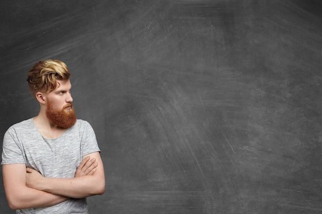 Ujęcie w głowę modnego rudowłosego młodego mężczyzny z modną fryzurą i gęstą brodą, ubranego niedbale, stojącego w prawym dolnym rogu pustej tablicy, trzymając ręce skrzyżowane i odwracając wzrok