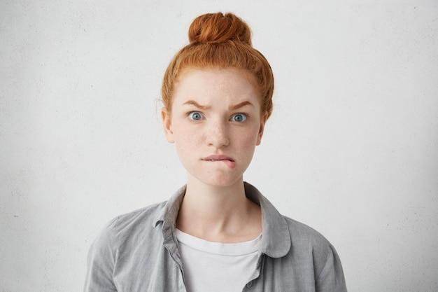 Ujęcie w głowę niespokojnej rudej piegowatej dziewczyny rasy kaukaskiej unoszącej brwi i gryzącej dolne wargi o wystraszonym, nerwowym lub złym spojrzeniu, czekającej na coś z niecierpliwością, pozującej odizolowanej